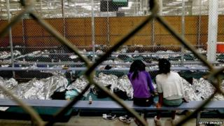 Two young girls watch a World Cup soccer match on a television from their holding area where hundreds of mostly Central American immigrant children are being processed and held at the US Customs and Border Protection Nogales Placement Center in Nogales, Arizona 18 June 2014