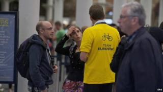 Eurostar worker helping passengers at St Pancras station in London