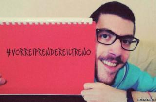 """Iacopo Melio holds up a sign saying """"#VorreiPrendereilTreno"""", which means """"I would like to take the train"""""""