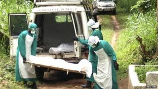 Health workers carry the body of an Ebola victim in Sierra Leone (25 June 2014)