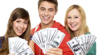 Three teens hold up hundred dollar bills.