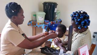 Alice Yamoah-Grant examines a baby