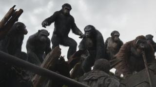 Caesar (standing) and friends in Dawn of the Planet of the Apes