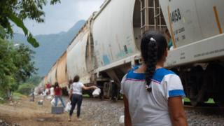 Women stand by the railway tracks in La Patrona ready to throw food to migrants on the train