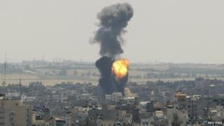 Smoke and flames are seen following what witnesses said was an Israeli air strike in Gaza City on 16 July 2014