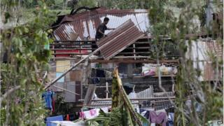 A resident fixes his house which was damaged by Typhoon Rammasun on Wednesday in Batangas city, south of Manila, Philippines, Thursday, on 17 July 2014.