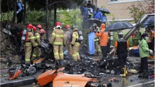 Firefighters inspect the wreckage of a helicopter which crashed near an apartment complex and school in Gwangju, South Korea, Thursday, on 17 July 2014.