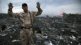 People inspect the crash site of a passenger plane near the village of Grabove, Ukraine