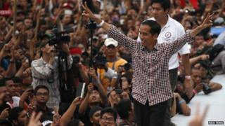 Indonesian presidential candidate Joko Widodo gestures to his supporters after delivering a speech at Gelora Bung Karno stadium in Jakarta on 5 July, 2014