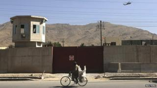 A Nato helicopter flies overhead at the site of the attack outside the counter-narcotics office near Kabul International airport