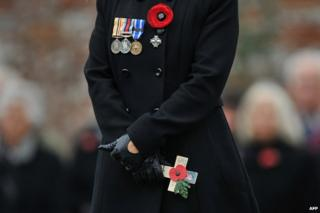 Kirianne Curley holds a cross of remembrance for her husband Corporal Stephen Paul Curley from 40 Commando Royal Marines who died whilst serving in with British troops in Afghanistan in 2010, during a service to mark Armistice Day, in Royal Wootton Bassett, in south-east England, on November 11, 2011