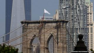 An NYPD helicopter flies over the Brooklyn Bridge inspecting white flags that have been placed on the top in Brooklyn, New York on 22 July 2014