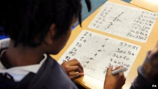 A primary school pupils works out sums in the classroom