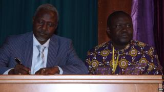 Exiled Centrafrican former general and representative of the Seleka opposition coalition Mohamed Moussa Dhaffane (L) and Patrice-Edouard Ngaissona, former Central African Youth and Sports Minister and self-declared political coordinator for the Anti-Balaka Christian militia sign a cease-fire agreement during a forum gathering key players in the Central African conflict, on July 23, 2014, in Brazzaville