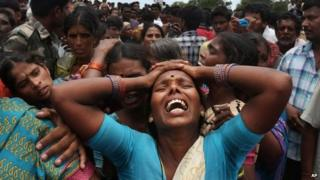 A relative of a victim cries at the site of a train that crashed into a school bus in Medak district in the southern Indian state of Telengana, Thursday, July 24, 2014.