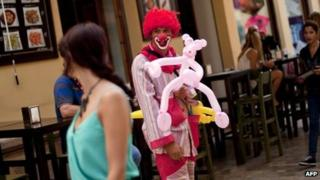 David (C), unemployment for one year, dresses as a clown and busks on the street in a bid to survive economically in Malaga
