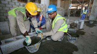 Migrant labourers work on a construction site in Doha, Qatar - 3 October 2013