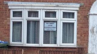 A sign saying 'Go away Love Productions, we don't want you filming here' in a window on the street