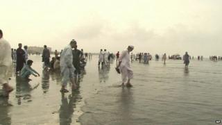 Members of family stand watching rescue operation on Karachi beach on 31 July 2014