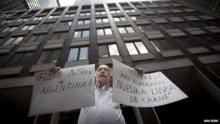 A protester holds up signs outside the office of a court-appointed mediator in New York on 30 July, 2014 reading