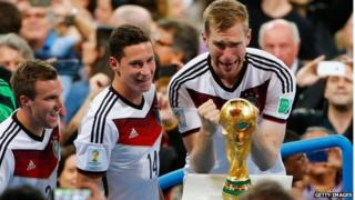 Members of Germany's winning World Cup football team with trophy