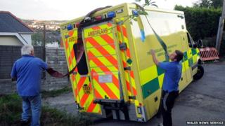 Workers throw a securing strap over the back of the ambulance