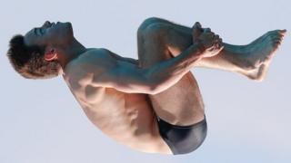 Tom Daley somersaults whilst diving