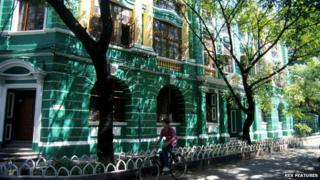 A man cycles past one of the old colonial buildings in Shamian Island