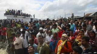 Bangladeshi onlookers gather near the scene where an overloaded ferry capsized in the Padma river in Munshiganj, some 30 kilometres (20 miles) south of the capital Dhaka, on August 4, 2014.