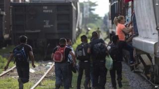 Immigrants run to jump on a train during their journey toward the U.S.-Mexico border, in Ixtepec, Mexico 12 July 2014