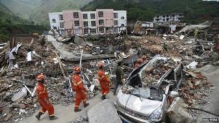 Rescue workers walk past debris of houses at an earthquake zone in Ludian county, Zhaotong, Yunnan province, on 5 August 2014