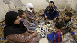 Mohammed al Hassan (back), 32, his wife Rana, and their family eat breakfast at home in a refugee camp in Amman on 29 May 2014
