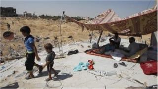 Children walk away from a makeshift shelter in Gaza. Adults are sitting under the shelter