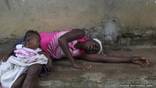A woman cries over teh death of a relative from ebola with her daughter on her lap
