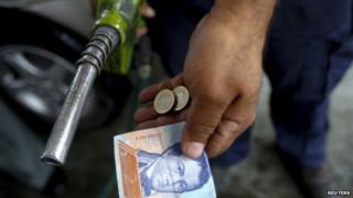 A worker at a petrol station in Venezuela shows the money used to pay for filling the tank