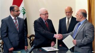 Iraqi President Fuad Masum (2nd L) shakes hands with deputy parliamentary speaker Haidar al-Abadi who has been tasked with forming a government ( image from Iraqi state TV)