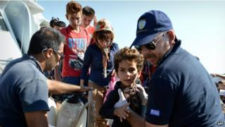 Greek coastguards help refugees disembark from a rescue boat