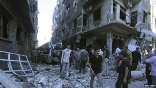 Residents inspect a site hit by what activists said were two air strikes by forces loyal to President Assad in Ghouta - 3 August 2014