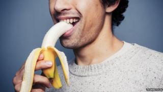 man consuming a banana