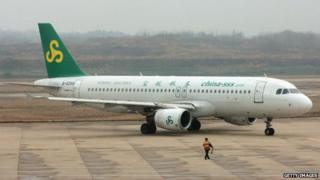 A worker directs an airplane from Spring Airlines at the Nanjing Airport on 8 February 2007 in Nanjing of Jiangsu Province, China