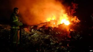 A firefighter stands by debris of MH17