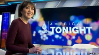 Presenter of Al Jazeera America in front of studio backdrop.
