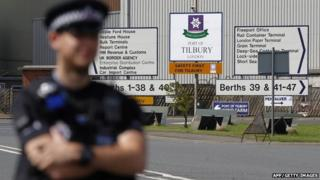 A policeman stands guard outside the entrance to Tilbury Docks