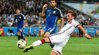 Mario Goetze shoots to score a goal against Argentina