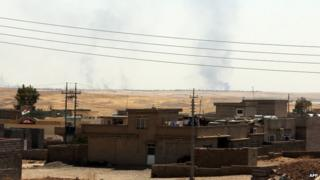Smoke rises in distance after a US air strike near Mosul dam on 17 August 2014