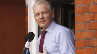Julian Assange reads a statement to the media from the window of the Ecuadorean embassy
