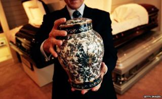 A man holds an ornate urn