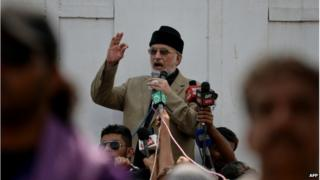 """Canada-based preacher Tahirul Qadri is surrounded by Pakistani supporters as he addresses demonstrators in front of the Parliament during the """"Revolution March"""" protest in Islamabad on 20 August 2014."""