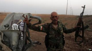 A peshmerga fighter flashes the sign for victory next to the remains of a car, bearing an image of the jihadist flag