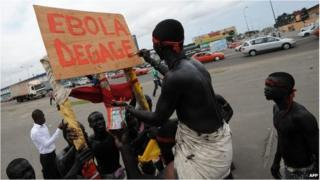"A man with a placard writing ""Ebola go away"" in Abidjan on 19 August."
